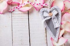 Decoratief hart op roze bloemblaadjes Stock Afbeeldingen