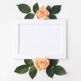 Decoratief kader met oranje rozen en groene bladeren Vlak leg Hoogste mening Stock Fotografie