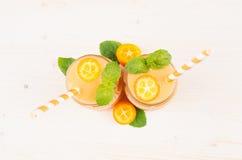 Decoratief kader van oranje citrusvruchtenkumquat fruit smoothie in glaskruiken met stro, muntblad, leuke rijpe bes, hoogste meni Stock Afbeelding