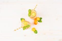 Decoratief kader van oranje citrusvruchtenkumquat fruit smoothie in glaskruiken met stro, muntblad, leuke rijpe bes, hoogste meni Stock Fotografie