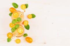 Decoratief kader van oranje citrusvruchtenkumquat fruit smoothie in glaskruiken met stro, muntblad, leuke rijpe bes, hoogste meni Royalty-vrije Stock Foto's