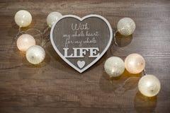 Decoratief met de hand gemaakt hart en lichten op de houten lijst Royalty-vrije Stock Afbeeldingen