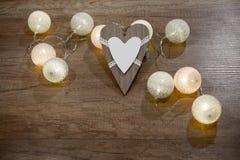 Decoratief met de hand gemaakt hart en lichten op de houten lijst Stock Afbeeldingen