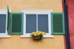 Decoratief wit venster op een oude oranje gipspleistermuur Stock Afbeeldingen