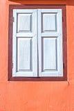 Decoratief wit venster op een oude oranje gipspleistermuur Stock Foto