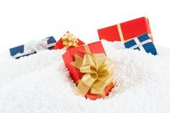 Decoratieve blauwe en rode giftdoos in de sneeuw Op wit Royalty-vrije Stock Fotografie