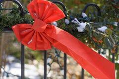 Decoratieve bowtie van het Kerstmis rode lint met sneeuw die in de wind slingeren Royalty-vrije Stock Foto