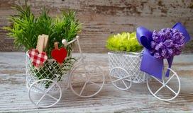 Decoratieve comfortabele fietsen met manden, bloemen, boog en houten harten Royalty-vrije Stock Foto