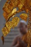 Decoratieve gouden bladeren met een mediterende monnik op de achtergrond stock fotografie
