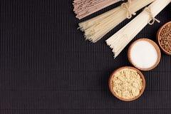 Decoratieve grens van bundels ruwe noedels met ingrediënt in houten kommen op zwarte gestreepte matachtergrond met exemplaar ruim Stock Fotografie