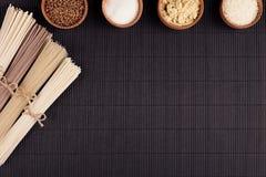 Decoratieve grens van bundels ruwe noedels met ingrediënt in houten kommen op zwarte gestreepte matachtergrond met exemplaar ruim Royalty-vrije Stock Foto's