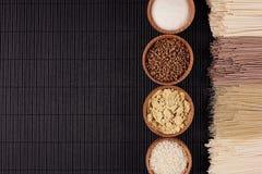 Decoratieve grens van bundels ruwe noedels met ingrediënt in houten kommen op zwarte gestreepte matachtergrond met exemplaar ruim Stock Afbeelding