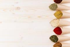 Decoratieve grens van divers close-up van poederkruiden in document hoeken op witte houten raad met exemplaarruimte Stock Fotografie