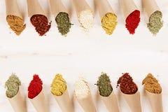 Decoratieve grens van divers close-up van poederkruiden in document hoeken op witte houten raad met exemplaarruimte Royalty-vrije Stock Afbeelding