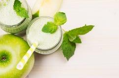 Decoratieve grens van groen appelfruit smoothie in glaskruiken met stro, muntbladeren, besnoeiingsappelen, hoogste mening Witte h Royalty-vrije Stock Foto's