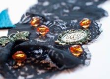 Decoratieve groene vlinder, oranje parels, kader en bergkristallen op zwart kant royalty-vrije stock fotografie