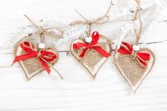 Decoratieve harten op snow-covered tak op houten achtergrond Royalty-vrije Stock Afbeeldingen