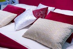 Decoratieve hoofdkussens van fluweel en brokaat op het bed in de slaapkamer stock afbeeldingen