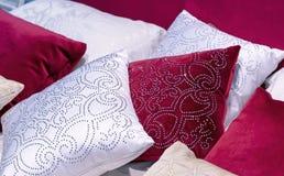 Decoratieve hoofdkussens van fluweel en brokaat op het bed in de slaapkamer stock afbeelding