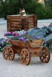 Decoratieve houten kar met bloemen in het zand tegen de put Royalty-vrije Stock Afbeelding