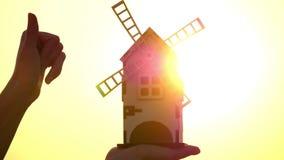 Decoratieve houten molen in de hand dichte omhooggaand van de vrouw Een vrouw roteert de bladen van een molen bij zonsondergang o stock videobeelden