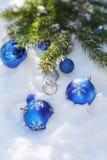 Decoratieve Kerstmisballen op de sneeuw en brunch van Kerstboom de openlucht Royalty-vrije Stock Afbeeldingen