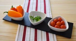 Decoratieve keukenwaren met peper, koriander en kersentomaten Stock Foto