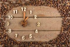 Decoratieve klok met houten die cijfers en pijlen van pijpjes kaneel worden gemaakt, die 1 uur, op een houten achtergrond en een  stock afbeeldingen