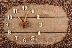 Decoratieve klok met houten die cijfers en pijlen van pijpjes kaneel worden gemaakt, die 11 uur, op een houten achtergrond en een stock fotografie