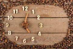 Decoratieve klok met houten die cijfers en pijlen van pijpjes kaneel worden gemaakt, die 5 uur, op een houten achtergrond en een  royalty-vrije stock afbeeldingen