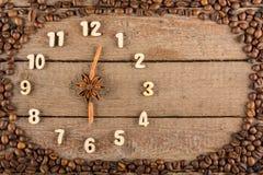Decoratieve klok met houten die cijfers en pijlen van pijpjes kaneel worden gemaakt, die 6 uur, op een houten achtergrond en een  royalty-vrije stock foto's