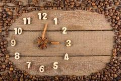 Decoratieve klok met houten die cijfers en pijlen van pijpjes kaneel worden gemaakt, die 3 uur, op een houten achtergrond en een  royalty-vrije stock foto