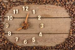 Decoratieve klok met houten die cijfers en pijlen van pijpjes kaneel worden gemaakt, die 8 uur, op een houten achtergrond en een  royalty-vrije stock afbeelding
