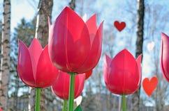 Decoratieve kunstmatige roze tulpen en harten tegen blauwe hemel Stock Fotografie