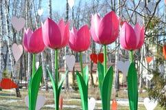 Decoratieve kunstmatige roze tulpen en harten tegen blauwe hemel Stock Afbeeldingen