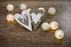 Decoratieve met de hand gemaakte harten en lichten op de houten lijst Royalty-vrije Stock Afbeelding