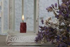 Decoratieve metaallantaarn binnen welke brandwonden de kaars, met bloemen stock fotografie