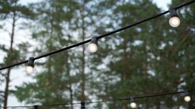 Decoratieve openluchtkoordlichten die in de tuin bij nacht hangen of tijd gelijk maken stock footage