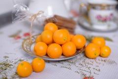 Decoratieve oranje mandarins, mandarijnen, kop thee, huismandarins, kleine mandarines stock fotografie