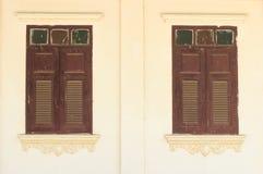 Oude houten vensters op een oude gipspleistermuur Stock Afbeelding