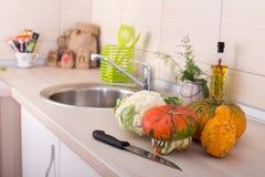 Decoratieve pompoenen op keukencountertop Stock Afbeeldingen