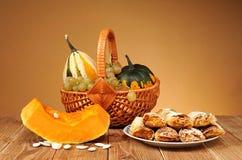 Decoratieve pompoenen in rieten manden en gebakjes Royalty-vrije Stock Foto's