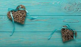 Decoratieve rieten harten van grijze kleur met een blauw lint op w Royalty-vrije Stock Afbeelding