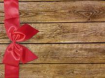 Decoratieve rode lint en boog over houten achtergrond Vakantieachtergrond met copyspace Oude houten achtergrond met mooie boog Royalty-vrije Stock Fotografie