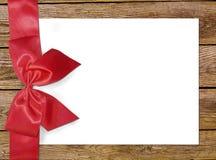 Decoratieve rode lint en boog over houten achtergrond Vakantieachtergrond met copyspace Oude houten achtergrond met mooie boog Royalty-vrije Stock Afbeelding