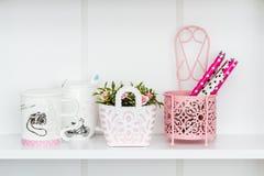 Decoratieve Roze Voorwerpen op Witte Plank stock foto