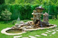 Decoratieve steenfontein met watermolen en tuinbeeldjes Het ontwerp van het landschap royalty-vrije stock afbeelding