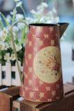 Decoratieve theepot op houten plank met een bloem als achtergrond Stock Foto's