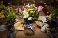 Decoratieve verse boeketten van rozen en wildflowers in ontwerperflessen handmade Stock Fotografie