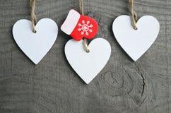 Decoratieve witte houten Kerstmisharten en rode vuisthandschoen op grijze rustieke houten achtergrond met exemplaarruimte Stock Foto's